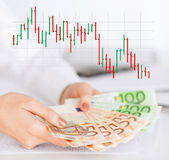 Close up of woman hands with chart and money. Business, people and finances concept - close up of woman hands holding euro money over gray background with forex stock illustration