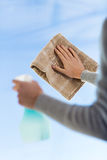 Close up of woman hands cleaning window with cloth Stock Photos