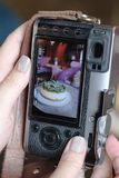 A woman takes a photograph of the cake using a mirrorless camera royalty free stock image