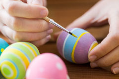 Close up of woman hands coloring easter eggs Stock Images