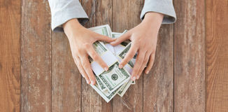 Close up of woman hands counting us dollar money. Business, finance, saving, banking and people concept - close up of woman hands counting us dollar money on Royalty Free Stock Photos