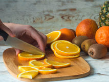 Close up woman hands cutting fresh orange with knife and wooden chopping board Stock Images