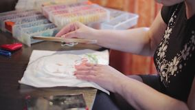 Woman hands doing embroidery cross-stitch. Close up of woman hands doing embroidery cross-stitch stock footage