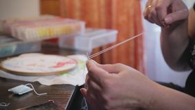Woman hands doing embroidery cross-stitch. Close up of woman hands doing embroidery cross-stitch stock video footage