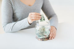Close up of woman hands and dollar money in jar Royalty Free Stock Images