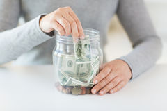 Close up of woman hands and dollar money in jar Royalty Free Stock Photos