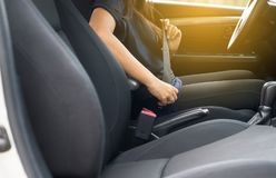Close up of woman hands fastening or putting seat belt in car,Transportation and vehicle concept stock images