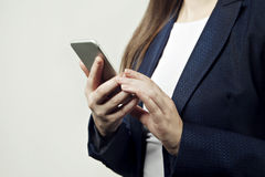 Close-up of woman hands hold phone, woman wears suit. Aga Royalty Free Stock Photos