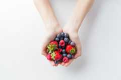 Close up of woman hands holding berries. Healthy eating, dieting, vegetarian food and people concept - close up of woman hands holding berries at home Stock Photography