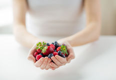 Close up of woman hands holding berries. Healthy eating, dieting, vegetarian food and people concept - close up of woman hands holding berries at home Stock Image