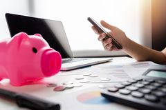 Close up of woman hands holding cell phone. Pink Piggy Bank, Laptop, Calculator, business chart and graph document on desk. Debt Royalty Free Stock Images