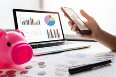 Close up of woman hands holding cell phone. Pink Piggy Bank, Laptop, Calculator, business chart and graph document on desk. Debt Stock Photography