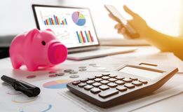 Close up of woman hands holding cell phone. Pink Piggy Bank, Laptop, Calculator, business chart and graph document on desk. Debt royalty free stock image