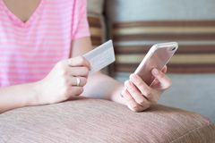 Close up woman hands holding credit card and using cell phone fo. R online shopping on sofa in the living room of the house Royalty Free Stock Image