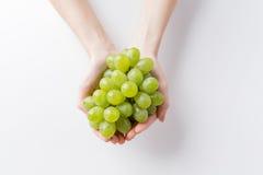 Close up of woman hands holding green grape bunch Stock Photos