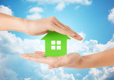 Close up of woman hands holding green house. Eco, people and real estate concept - close up of woman hands holding green house over blue sky and clouds Royalty Free Stock Photos