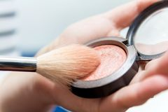 Close up of woman hands holding makeup brush and blush box.  Stock Photo