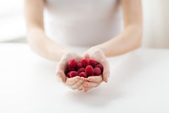 Close up of woman hands holding raspberries. Healthy eating, dieting, vegetarian food and people concept - close up of woman hands holding raspberries at home Stock Images