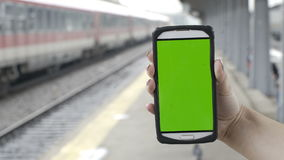 Close-up of woman hands holding smartphone with green screen chroma key in train station. Closeup of woman hands holding smartphone with green screen chroma key stock video footage