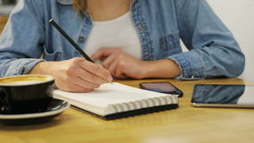 Close-up woman hands holding smartphone and writing in notebook in the cafe with wooden furniture stock video