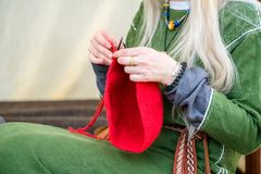 Close-up of woman hands knitting red wool hat, while wearing rural linen clothing. Freelance creative working and living concept stock photos