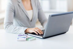 Close up of woman hands with laptop and money Royalty Free Stock Photography