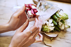Close-up of woman hands opening a present box, celebrating Valentine`s Day, birthday. Bouquet of flowers on wooden table.  Royalty Free Stock Images