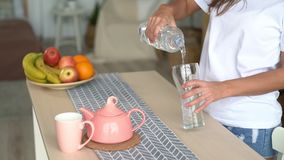 Close up woman hands opens bottle, pours pure water into glass on table, slow motion. Kettle, cup and fruit stands on kitchen table stock footage