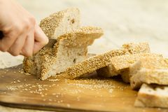Close up of woman hands slicing a loaf of homemade bread with sesame seeds on a wooden cutting board in selective focus on wooden stock photography