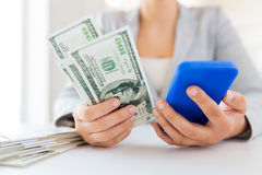 Close up of woman hands with smartphone and money Royalty Free Stock Images