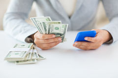 Close up of woman hands with smartphone and money Stock Image