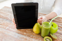 Close up of woman hands tablet pc and fruit juice Royalty Free Stock Photography