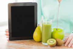 Close up of woman hands tablet pc and fruit juice Royalty Free Stock Images