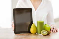 Close up of woman hands tablet pc and fruit juice Royalty Free Stock Photos