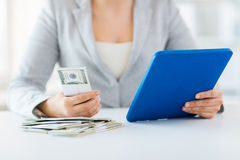 Close up of woman hands with tablet pc and money Stock Photo
