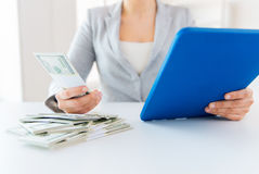 Close up of woman hands with tablet pc and money Stock Image