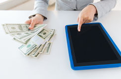 Close up of woman hands with tablet pc and money Royalty Free Stock Photography