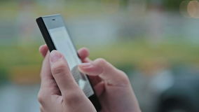 Close up of woman hands texting, sending sms on smartphone in city. Bokeh light stock video footage