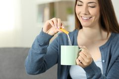 Woman throwing sugar into a mug. Close up of a woman hands throwing sugar into a mug sitting on a couch in the living room at home Stock Photos