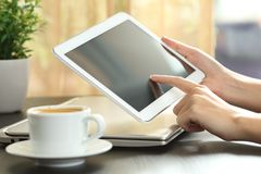 Woman hands touching a tablet screen on a table. Close up of a woman hands touching a tablet screen on a table stock images