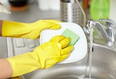 Close up of woman hands washing dishes in kitchen stock images