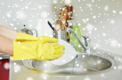 Close up of woman hands washing dishes in kitchen. People, housework, washing-up and housekeeping concept - close up of woman hands in protective gloves washing royalty free stock photo