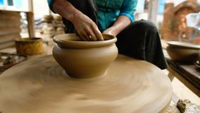 Woman hands working clay. Close up of woman hands working clay on potter`s wheel. Potter shapes the clay pot with hands on the potter`s wheel, craft factory stock video