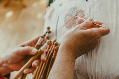 Close-up of woman hands works with bobbin lace, hand made crafting Laces Stock Photos