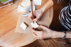 Close up of woman hands writing different notes stickers by wooden pencil. Young beautiful woman drawing various message for a bo Stock Images