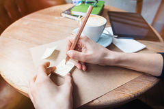 Close up of woman hands writing love notes stickies by wooden pencil. Young beautiful woman drawing love message for a boy friend Stock Photo