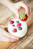 Close up of woman hands with yogurt and berries Stock Photos