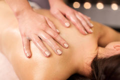 Close up of woman having back massage at spa. People, beauty, healthy lifestyle and relaxation concept - close up of beautiful young woman lying and having back Royalty Free Stock Photos