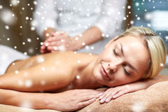 Close up of woman having back massage in spa. People, beauty, spa, winter and relaxation concept - close up of beautiful young woman lying with closed eyes and Royalty Free Stock Image