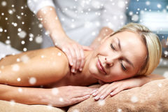 Close up of woman having back massage in spa. People, beauty, spa, winter and relaxation concept - close up of beautiful young woman lying with closed eyes and Stock Photos